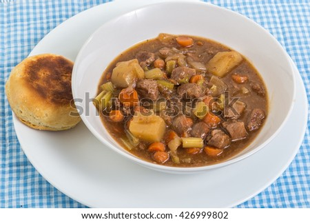 Overhead view of bowl of beef stew in white bowl on white plate with baked biscuit. Blue Gingham background. - stock photo