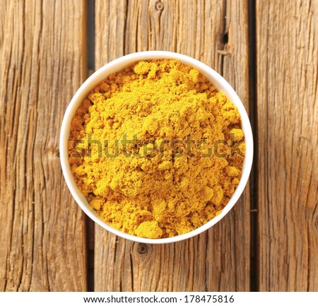 overhead view of bowl with curry powder - stock photo