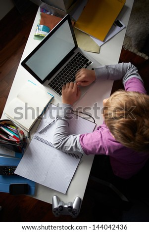 Overhead View Of Boy Studying In Bedroom Using Laptop - stock photo