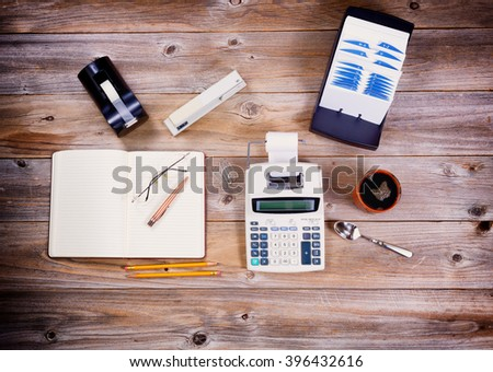 Overhead view of business desktop with supplies and objects from the past. Vignette effect on borders.  - stock photo