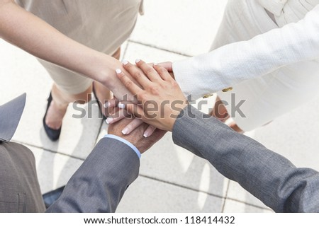 Overhead view of business team of businessman and businesswomen, men & women, hands together deal making agreement - stock photo