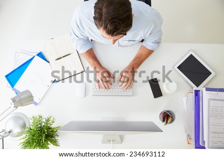 Overhead View Of Businessman Working At Computer In Office - stock photo