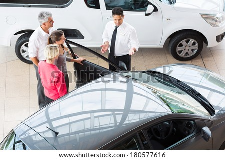 overhead view of car salesman showing new vehicle to customers - stock photo