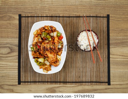 Overhead view of Chinese spicy chicken dish and rice in bowl with chopsticks placed on natural bamboo mate with rustic wooden boards underneath.    - stock photo