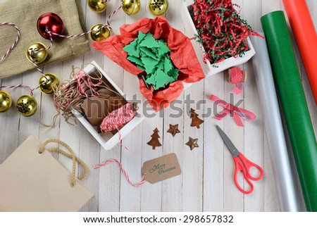Overhead view of Christmas wrapping supplies on a rustic wood table. Scissors, ribbon, bells, tags, paper rolls, gift bag, string, ornaments and crepe paper are displayed. - stock photo