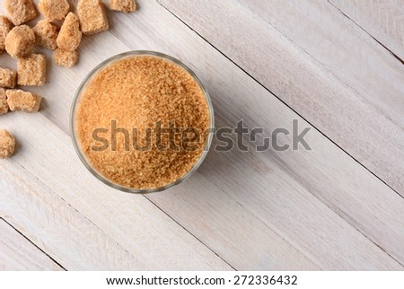 Overhead view of chunks of raw brown sugar and a bowl full of trubinado granules on a white wood table. - stock photo