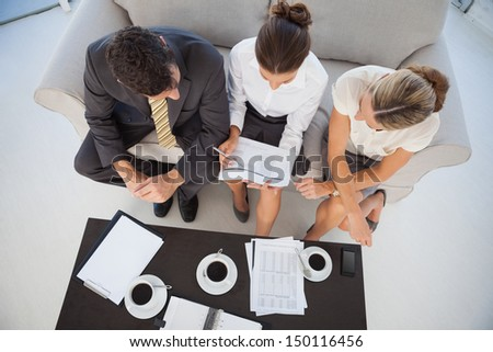 Overhead view of colleagues working and having coffee together in bright office - stock photo