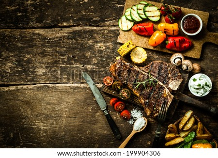 Overhead view of colorful roast vegetables, savory sauces and salt served with grilled t-bone steak on a rustic wooden counter in a country steakhouse - stock photo