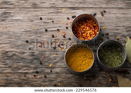 Overhead view of Colourful dried ground spices in bowls on old aged scored wooden surface in a country kitchen - stock photo