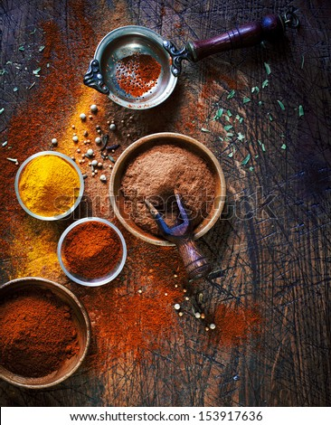 Overhead view of colourful dried ground spices in bowls spilling onto an old aged scored wooden surface in a country kitchen with a vintage sieve or strainer - stock photo