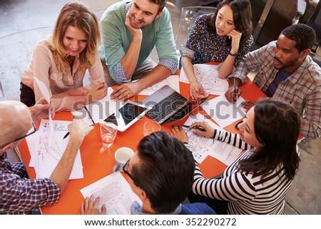Overhead View Of Designers Having Meeting Around Table - stock photo