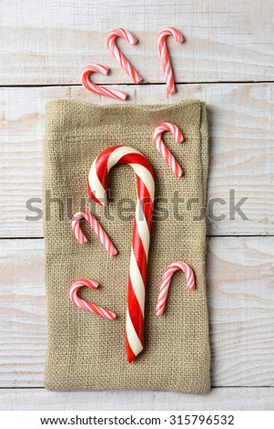 Overhead view of different sized Candy canes on a burlap bag and three on wood surface. On a rustic wood table in vertical format - stock photo