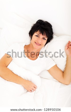 overhead view of elegant mid age woman lying on bed relaxing