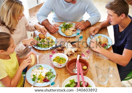 Overhead View Of Family Sitting At Table Enjoying Meal - stock photo