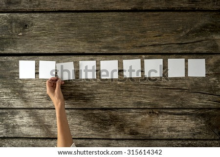 Overhead view of female hand placing nine blank white cards in a row on a rustic textured wooden boards. With copy space ready for your text or promotion. - stock photo