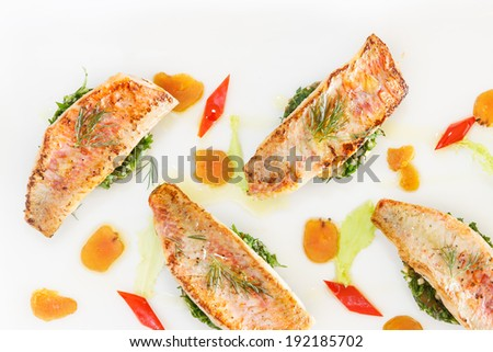 Overhead view of four healthy delicious grilled fish fillets seasoned with fresh herbs plated with colorful vegetables - stock photo
