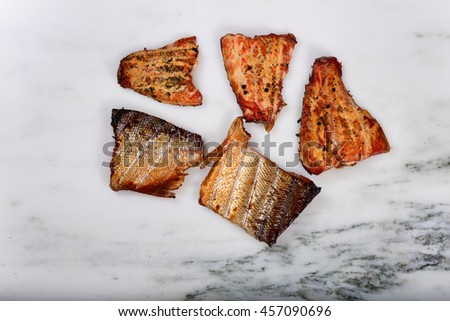 Overhead view of freshly smoked red salmon fillets on natural marble stone counter.
