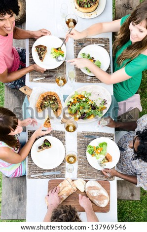 Overhead view of friends passing food at a table, outdoor garden lunch party celebration - stock photo
