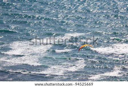 Overhead view of hang glider over rough ocean off Hawaii