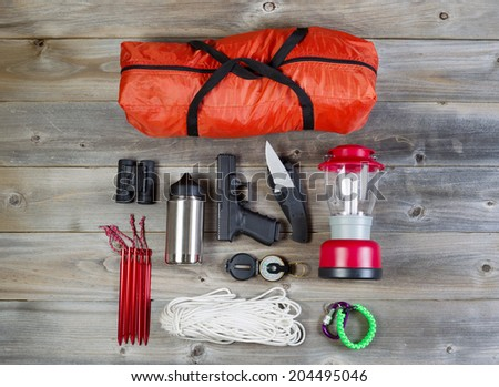 Overhead view of hiking gear and personal protection, pistol and knife, placed on rustic wood - stock photo
