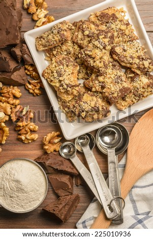 Overhead view of homemade chocolate walnut cookies with ingredients and kitchen utensils on a dark rustic wood table. - stock photo