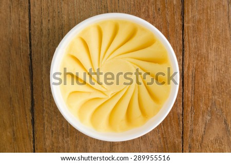Overhead view of  homemade Mango Italian ice cream tub on wooden background