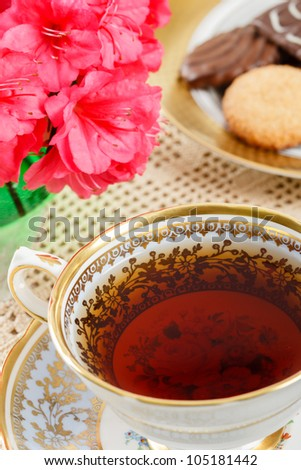 Overhead view of hot tea in a vintage teacup accented with azaleas and a plate of cookies in the background