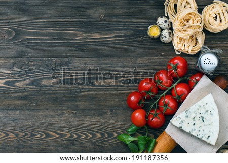 Overhead view of ingredients for an Italian pasta recipe on rustic wood boards with copyspace - stock photo