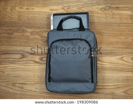 Overhead view of laptop computer, partially out of carry case, on rustic wooden boards - stock photo