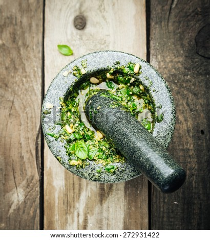 Overhead View of Making Pesto with Fresh Herbs and Oil in Stone Mortar and Pestle on Wooden Background - stock photo