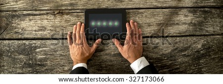Overhead view of male hand holding a digital tablet with five check boxes with green tick in them. Conceptual of survey, feedback and customer service. - stock photo