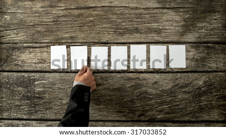 Overhead view of male hand in business suit placing seven blank white cards in a row on a rustic textured wooden boards. With copy space ready for your text or promotion. - stock photo