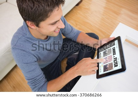 Overhead view of man using digital tablet in living room against smartphone app menu