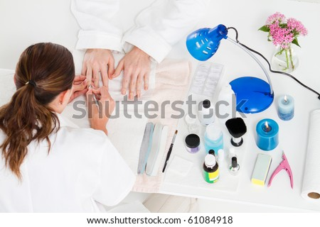 overhead view of manicurist working on client's fingernails - stock photo