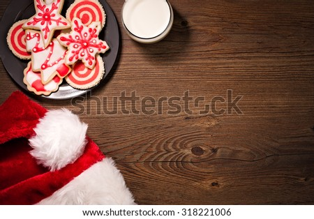 Overhead view of milk, Christmas cookies and a Santa Hat on a wooden background. - stock photo