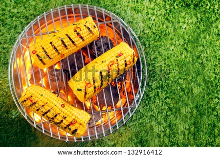 Overhead view of ripe yellow corn on the cob grilling over hot coals in a portable barbecue on a green lawn with copyspace - stock photo