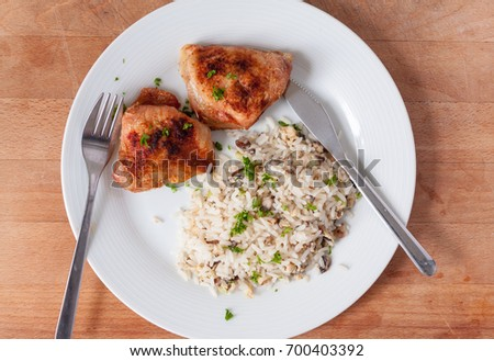 Overhead view of roast chicken thighs and mushroom rice on a white plate