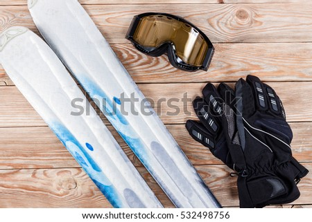 Overhead view of ski accessories placed on rustic wooden table. Items included ski, goggles and gloves. Winter sport leisure time concept.