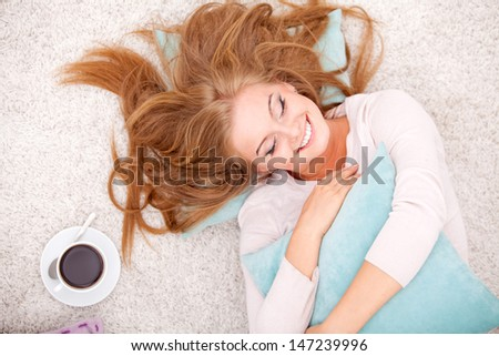 Overhead view of smiling woman lying on carpet with pillow and coffee at home - stock photo