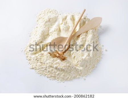 overhead view of soft wheat flour with wooden spoon and whisk