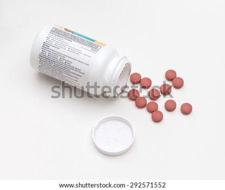Overhead view of spilled bottle of ibuprofen pills on a white background