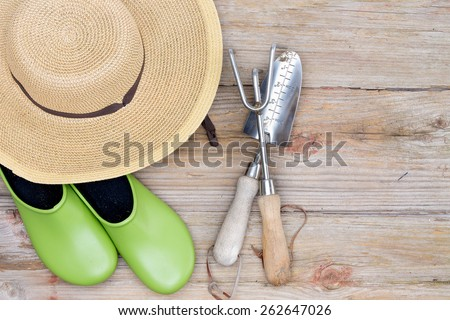 Overhead View of Straw Wide-Brimmed Hat, Pair of Green Gardening Shoes and Gardening Tools on Wooden Deck Background with Copy-space - stock photo