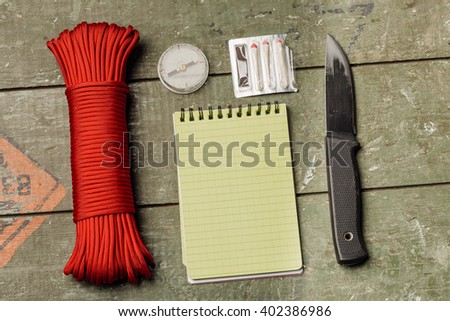 Overhead view of survival gear equipment to survive and Notebook with Pen.Items include knife, red rope, notepad, pen, compass, matches. Writing Notes for Traveller with wooden pallet background. - stock photo