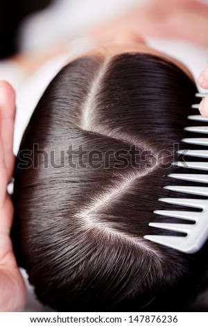 Overhead view of the top of a brunette woman showing a new creative hairstyle with a zig zag path with a portion of the hairdressers comb in view - stock photo