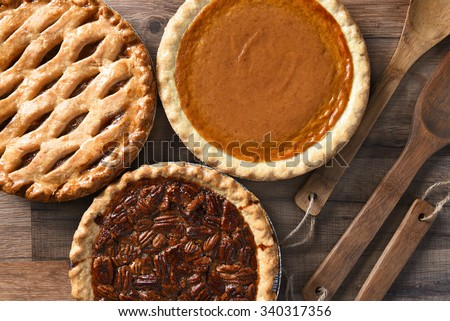 Overhead view of three pies for a Thanksgiving Holiday feast. Pecan, Apple and Pumpkin in horizontal format on wood table - stock photo