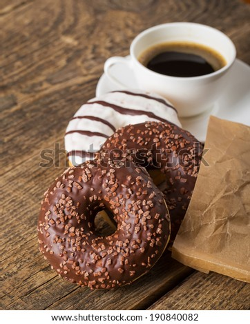 Overhead view of two tempting fresh doughnuts with their brown paper wrapping and a cup of strong black espresso coffee on a rustic wood table - stock photo