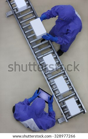 overhead view of two workers in blue uniforms working with boxes on packing line - stock photo