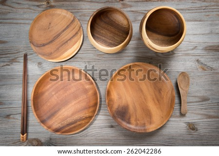 Overhead view of various design empty plates and sushi chopsticks on old wooden table. View of dining setting in vintage mood with dramatic light. - stock photo