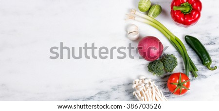 Overhead view of various whole vegetables and fruits, on right side of frame, on marble stone.