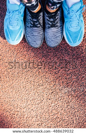 Overhead view of women's and men's brand sport shoes together in closeup, empty space on jogging track for your ad.